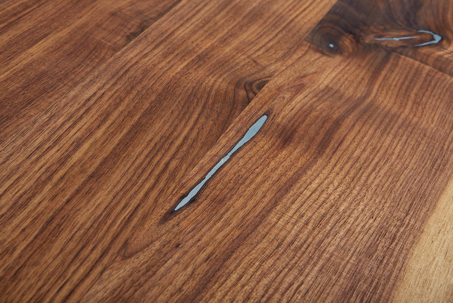 Esstisch Baumkante Nussbaum Detail mit Zinneinlage